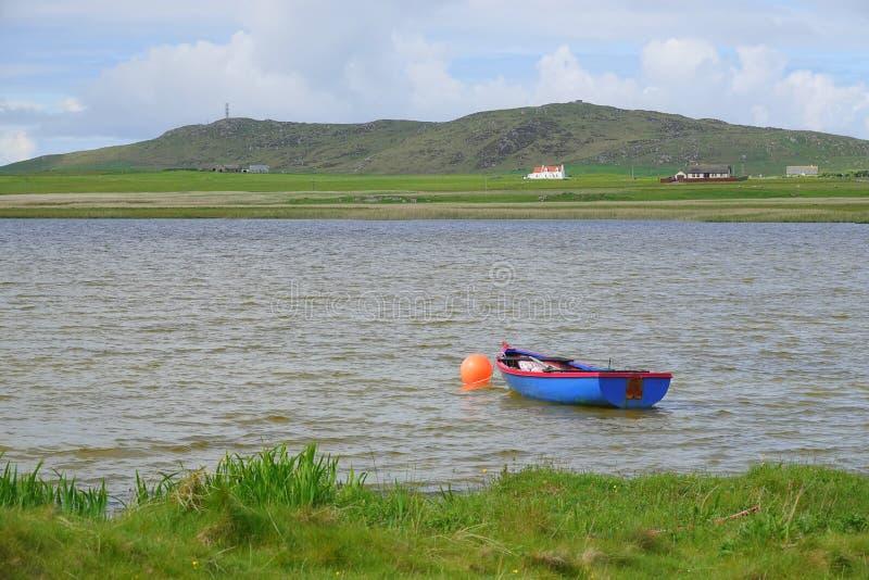 Blå jolle som förtöjas för att hålla flytande i sjön royaltyfri bild