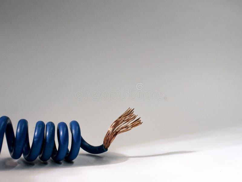 Blå kabel som vrids på vit bakgrund elektrisk isolerad tråd royaltyfri fotografi