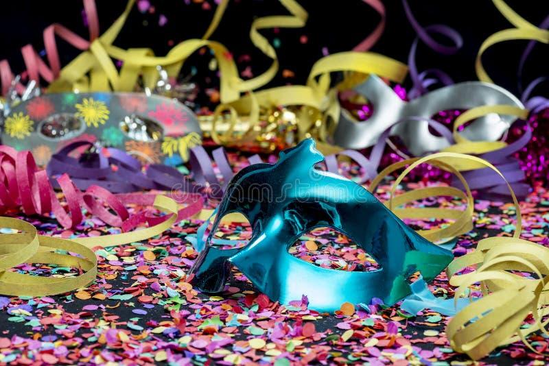 Blå karnevalmaskering över konfettier och mång--färgade banderoller royaltyfri foto