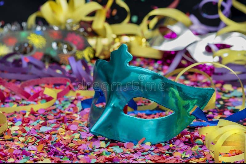 Blå karnevalmaskering över konfettier och mångfärgade banderoller arkivbild