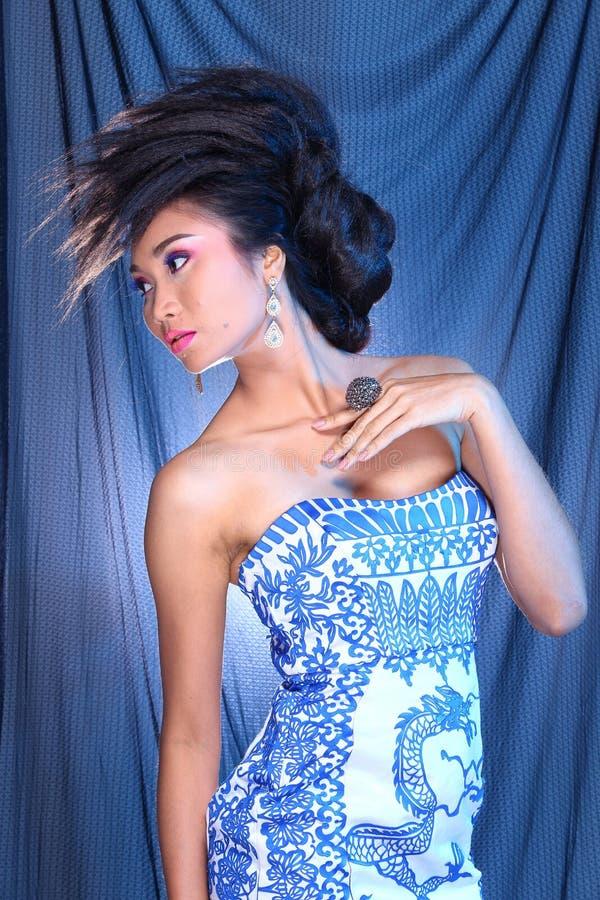 Blå klänning för boll för aftonkappa i asiatisk härlig kvinna med fashi arkivbild
