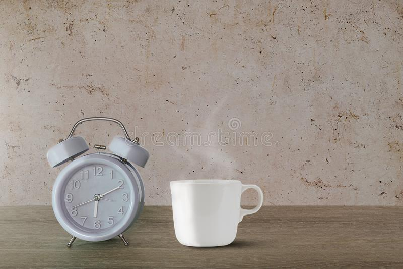 Blå klassisk ringklocka och varm kopp för vitt kaffe med ånga på tappningväggbakgrund arkivfoton