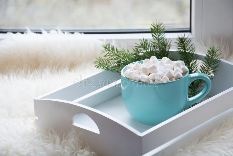 Blå kopp av varm choklad med marshmallowen på fönsterbräda Helgbegrepp Hem- stil bakgrundsjulen stänger upp röd tid royaltyfri fotografi