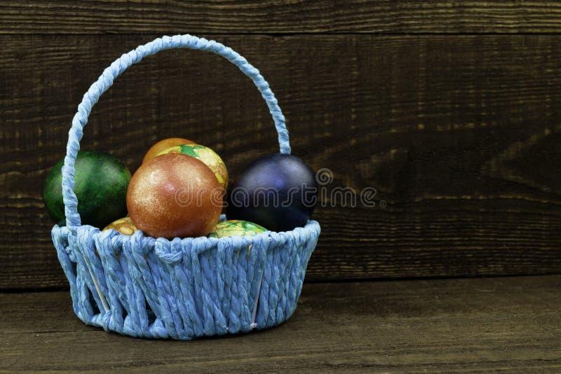 Blå korg med easter ägg på en mörk brun träbakgrund, kopieringsutrymme royaltyfri fotografi