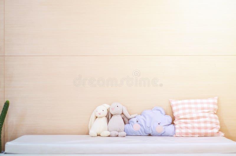 Blå kudde, gullig kanindocka i säng i sovrummet royaltyfri foto