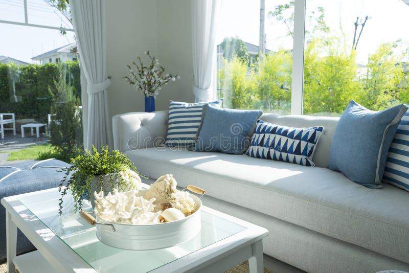 Blå kudde på den gråa soffan i vardagsrum arkivfoto