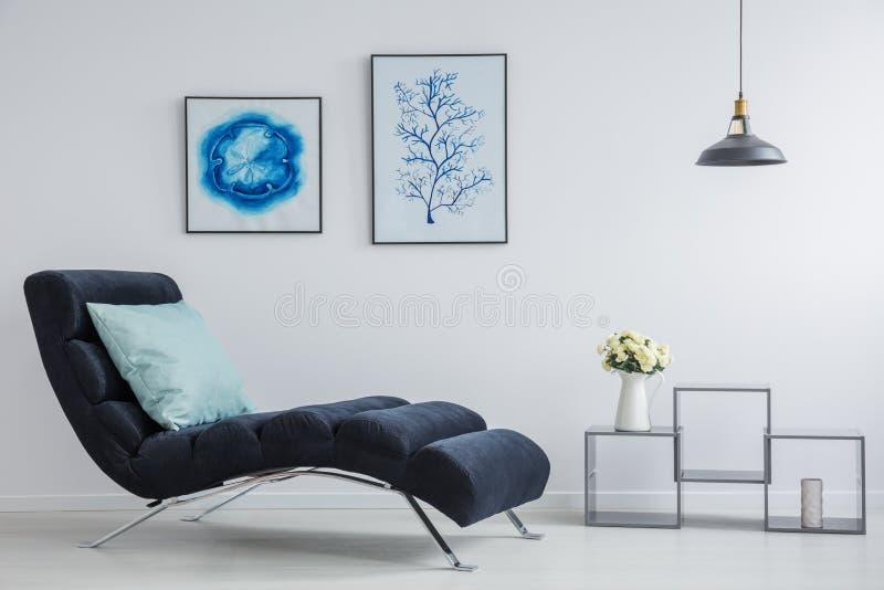 Blå kudde på svart chaisevardagsrum royaltyfri foto