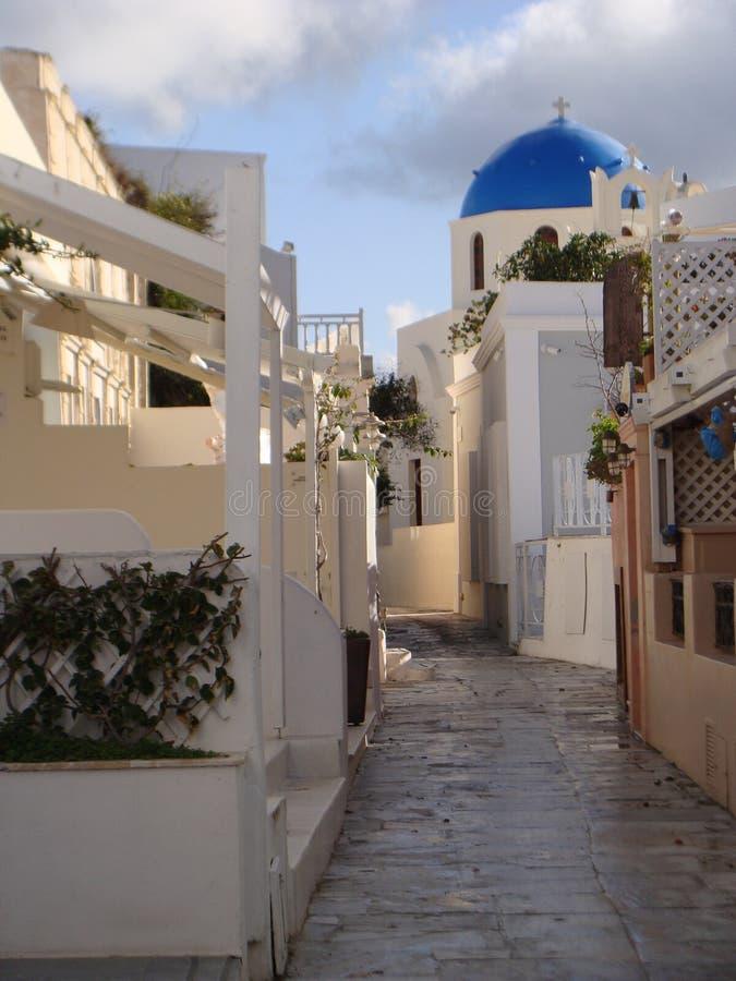 Blå kupolformig kyrka i bakgrunden av denna gata i Oia i Santorini, Grekland royaltyfria bilder