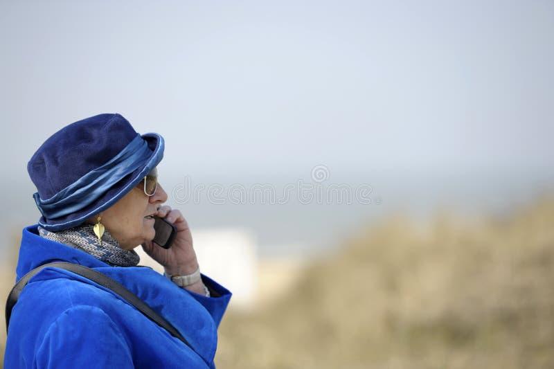 blå kvinna för pensionär för celltelefon royaltyfri bild