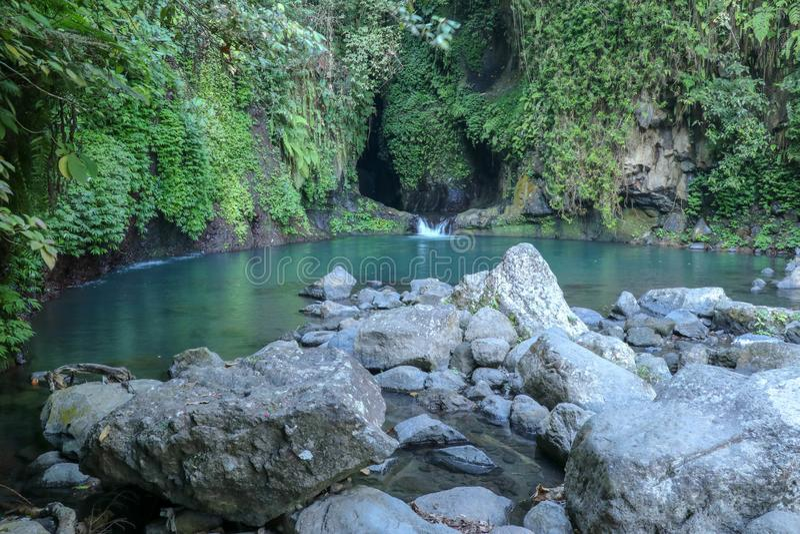 Blå lagun under vattenfallet på den Bali ön Naturlig sjö med härligt blått och grönt kulört vatten H?rligt naturligt landskap arkivbild