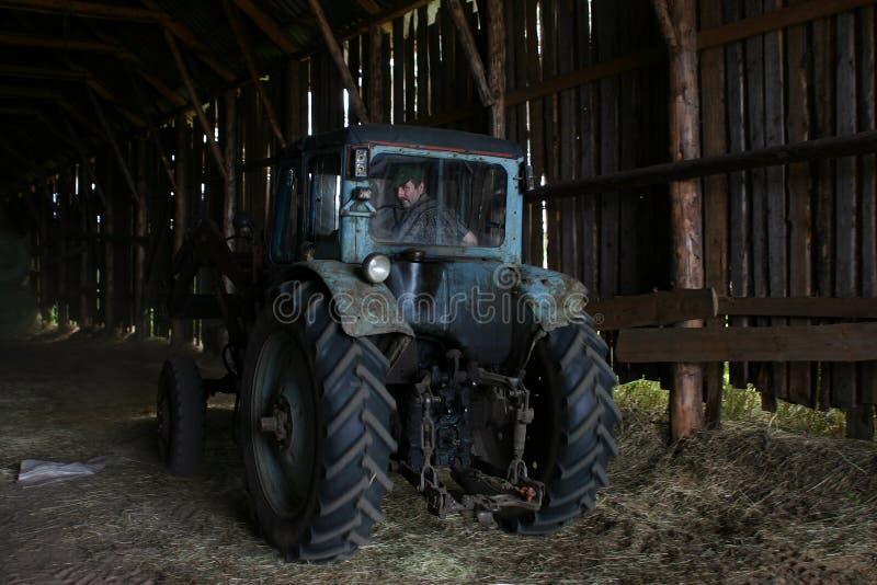 Blå lantgårdtraktor med traktorchauffören, under taket av hayloften arkivfoto