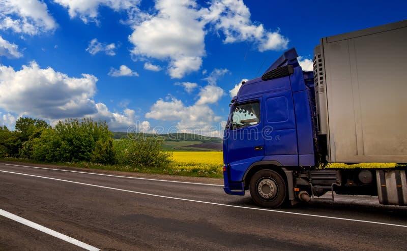 Blå lastbil på vägen i ett lantligt landskap, i bakgrunden arkivbilder