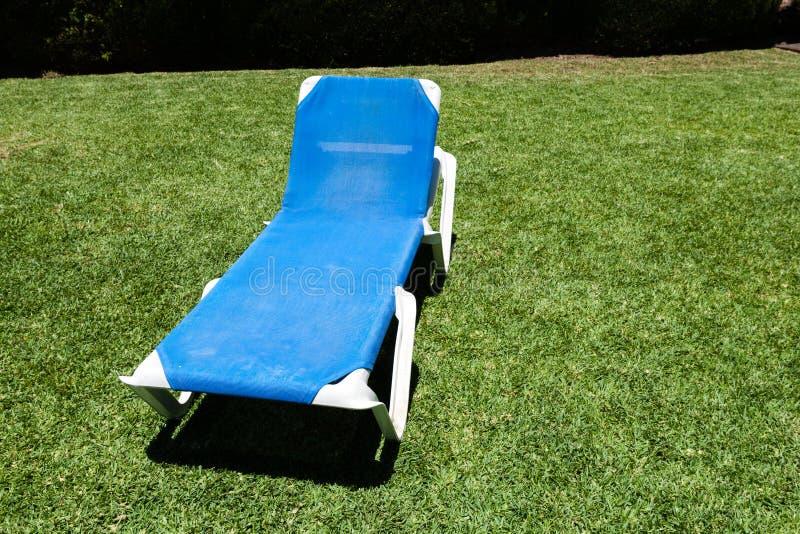 Blå lounger på en grön lawn royaltyfri foto