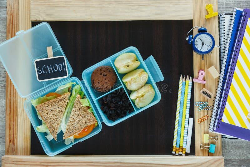 Blå lunchask för skola med den hemlagade smörgåsen, grönt äpple, kakor, blyertspennor, klocka, anteckningsböcker på tabellen ?ta  arkivfoton