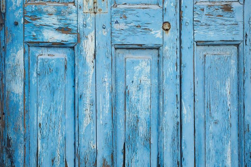 Blå målarfärg som av skalar dörren (textur) arkivbilder