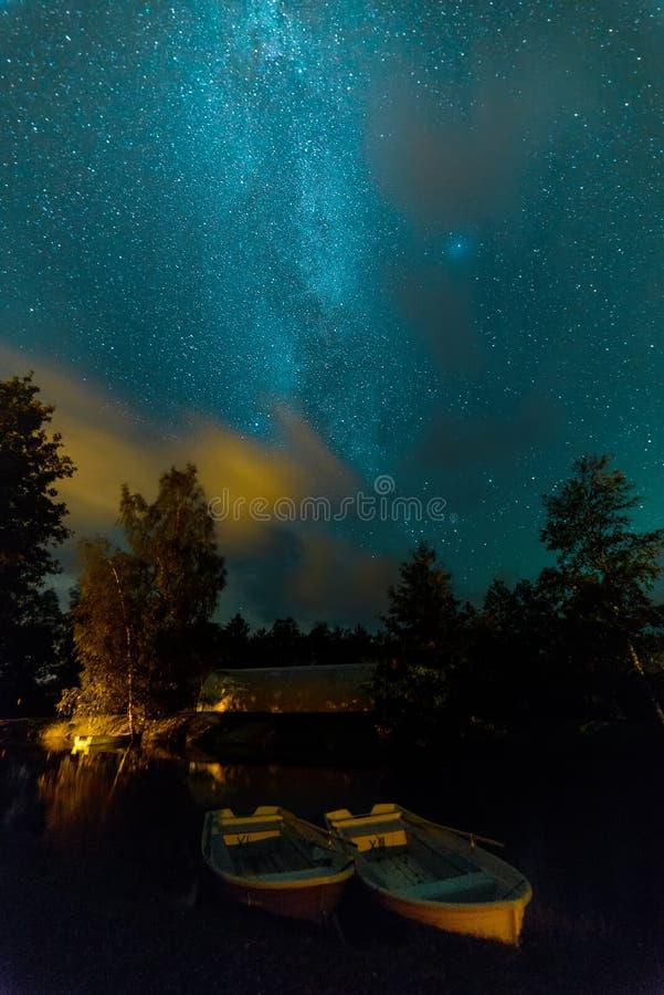 Blå mörk natthimmel med många stjärnor och fiskebåtar arkivbild