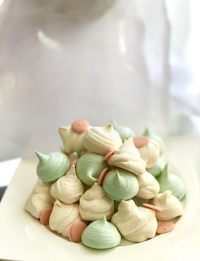 Blå maräng, vit rosa choklad, på en vit maträtt Efterr?tt p? en vit bakgrund S?t mat arkivbild