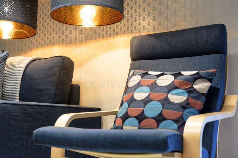 Blå mjuk stol med kudden, hög tillbaka läs- lampa ovanför huvudet interiorvardagsrum för bild 3d arkivfoto