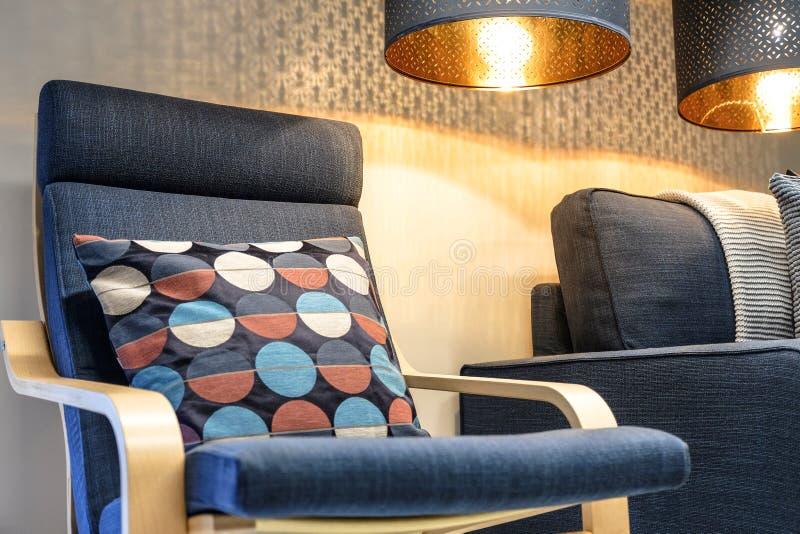 Blå mjuk stol med kudden, hög tillbaka läs- lampa ovanför huvudet interiorvardagsrum för bild 3d Sofaen med kudder arkivbild
