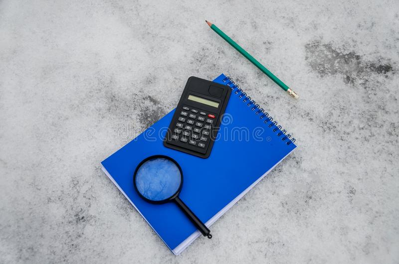 Blå notepad, räknemaskin, förstoringsapparat och grön blyertspenna på vit snöbakgrund royaltyfri fotografi