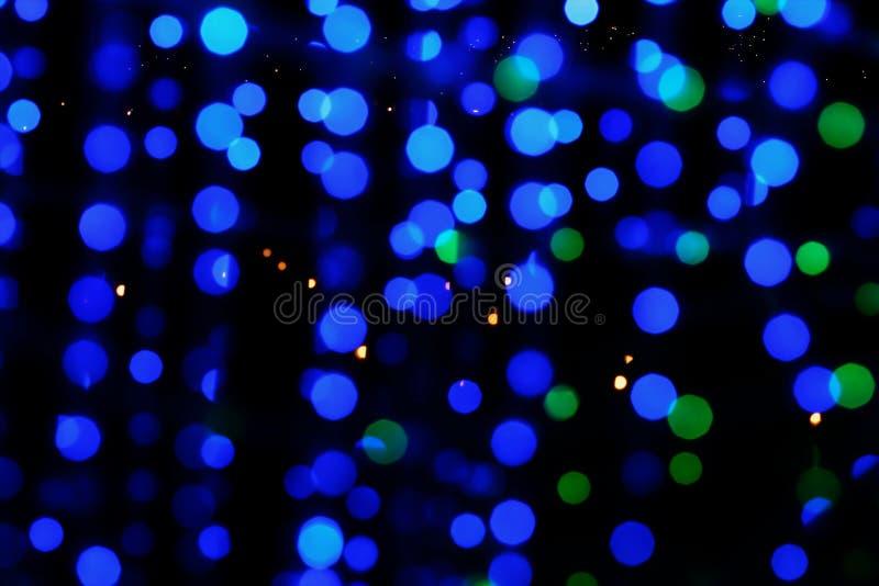 Blå och grön suddighetsbokeh från ljus på mörk natt royaltyfria bilder
