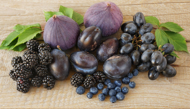 Blå och purpurfärgad mat Björnbär druvor, plommoner, blåbär, fikonträd på en träbakgrund royaltyfri bild