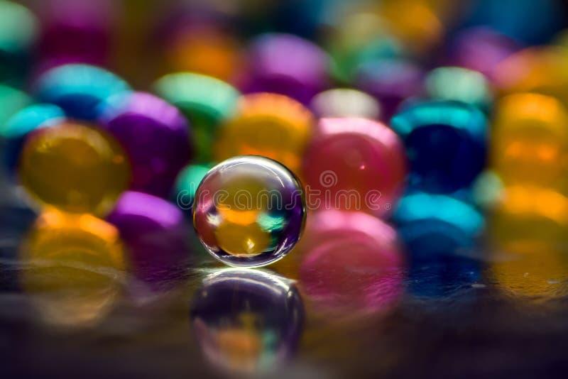 Blå och purpurfärgad orb med reflexion, mot en bakgrund av färgrika ballonger, abstrakt bakgrund royaltyfria foton