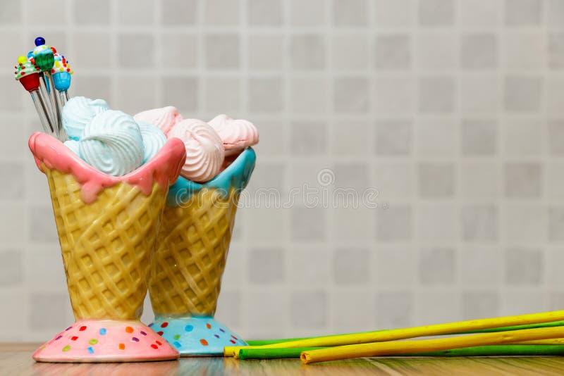 Blå och rosa maräng i rosa färg- och blåttkottarna med muffin-, gräsplan- och gulingpinnar på wood tabellvitbakgrund arkivbild
