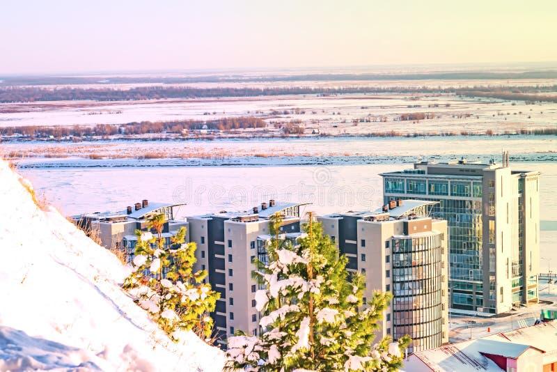 Blå och rosa solnedgånghimmel över den djupfrysta floden i vinter på horisonten med bostads- byggnader för höghus, fotografering för bildbyråer