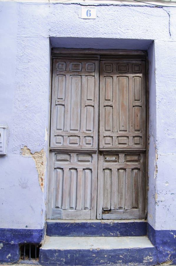 Blå och vit gammal dörr av ett hus i en by i Spanien royaltyfri fotografi