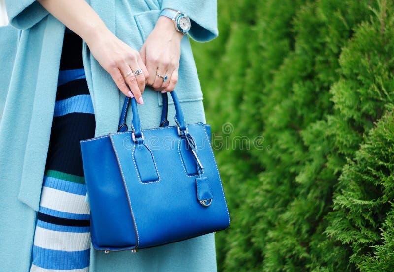 Blå påse och halsduk i kvinnliga händer Närbild Kvinna i lag och i en randig klänning utomhus Flicka med ett ljust stilfullt arkivbilder