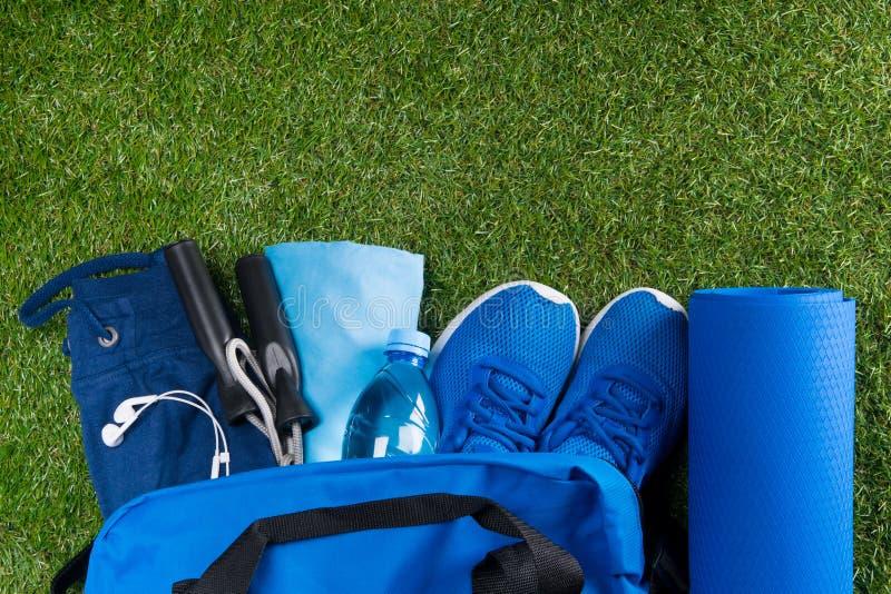 Blå påse på det gröna gräset, med en uppsättning av sportsaker och skor, vatten i flaskan och musik för lynnet arkivfoto
