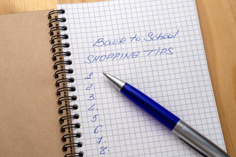 Blå penna på en anteckningsbok med ark i en bur Tecken - som är tillbaka till skola och shoppingspetsar royaltyfri foto