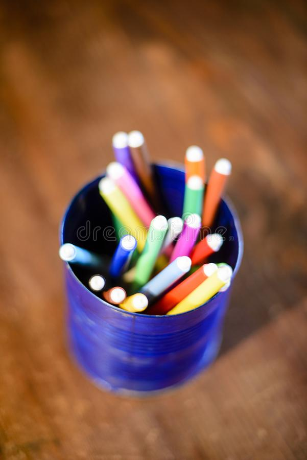 Blå pennhållare med kulöra markörer arkivbild