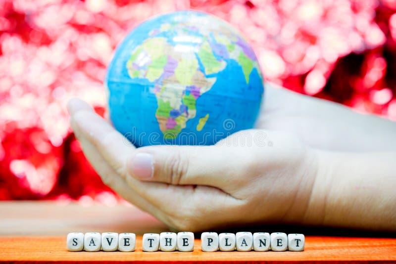 Blå planet i din hand på röd bakgrund arkivfoton