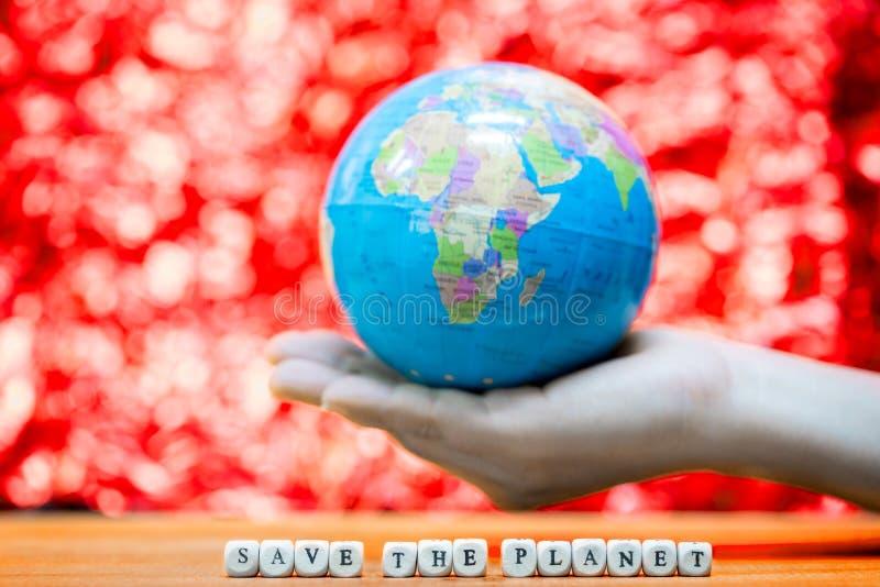 Blå planet i din hand på röd bakgrund royaltyfria foton