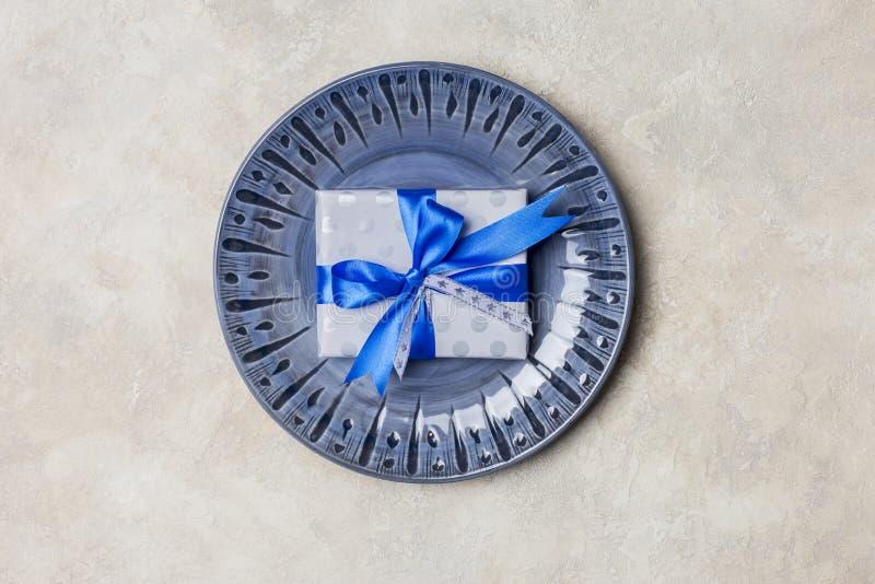 Blå platta med gåvaasken med den blåa pilbågen på vit bakgrund arkivfoton