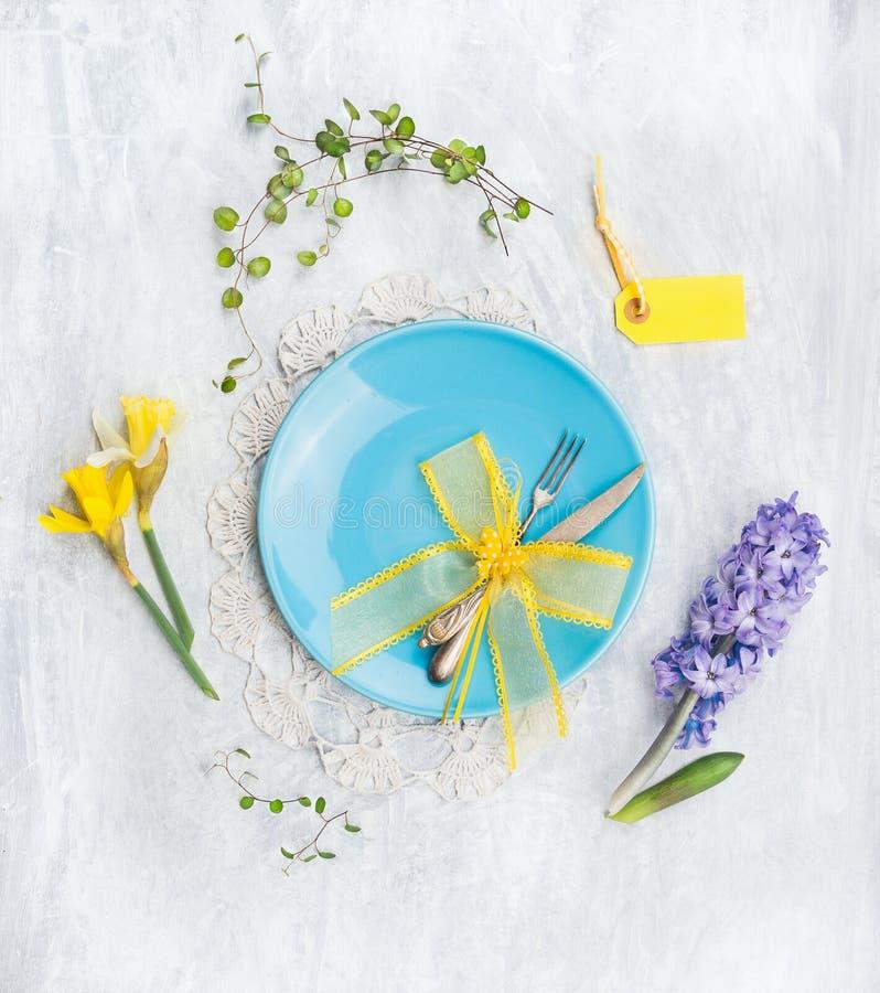 Blå platta med kniven, gaffeln, vårblommor och gul bandgarnering på grå träbakgrund royaltyfria bilder
