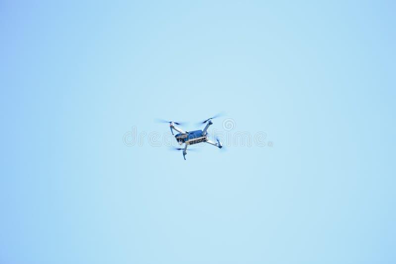 Blå quadrupter med propellrar flyger i himmel- och fotografilandskapen royaltyfri bild