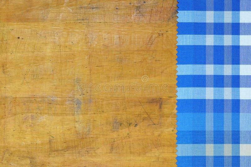 Blå rutig bordduk på träbakgrund royaltyfri bild