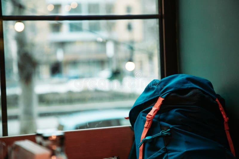 Blå ryggsäck nära fönster arkivbild