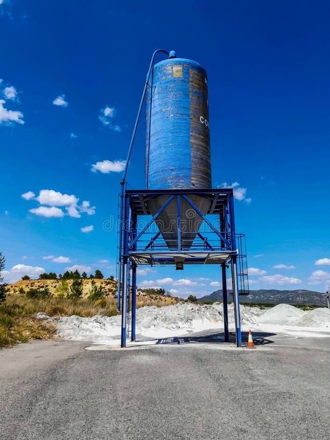 Blå silo av vitt cement på ett berg med liten vegetation royaltyfri bild