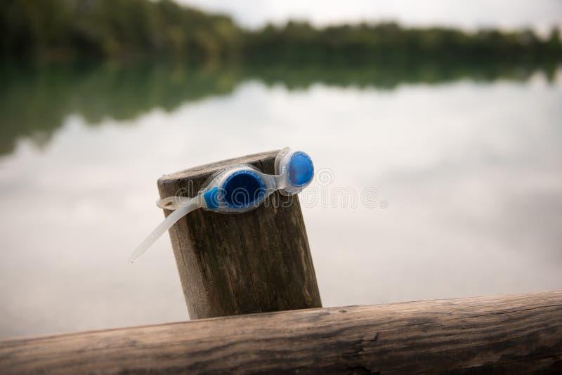 Blå simning googlar på en träpol med den stora sjön i bakgrund royaltyfria foton