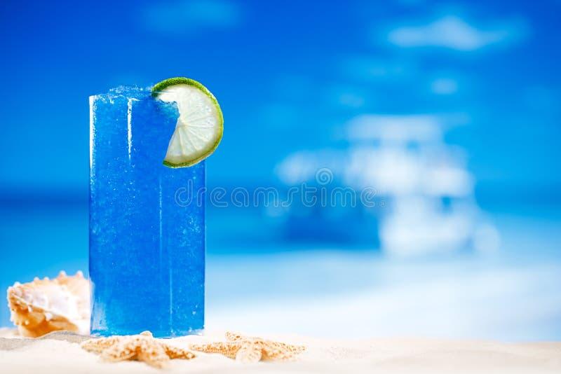Blå snöslaskisdrink i exponeringsglas med seascape arkivfoto