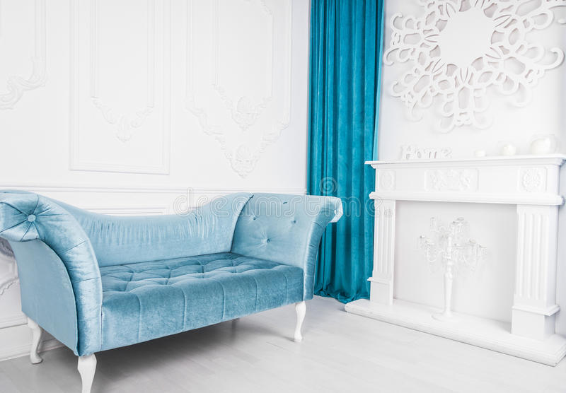 Blå soffa i det vita inre- och grå färggolvet venetian stil Dekorativ spis royaltyfri fotografi