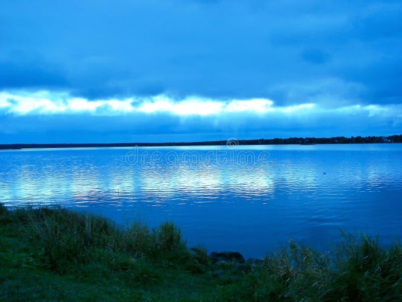 Blå solnedgång över vattnet royaltyfri bild