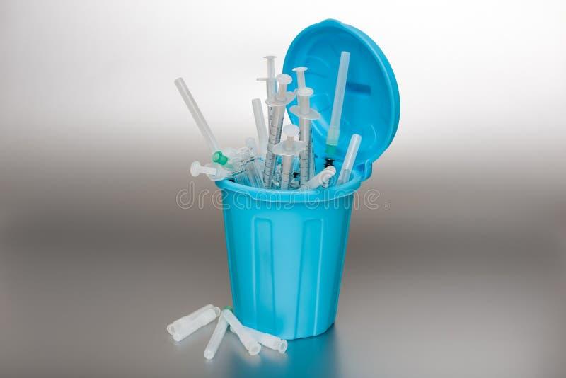 Blå soptunna med läkarundersökningavfalls arkivfoto