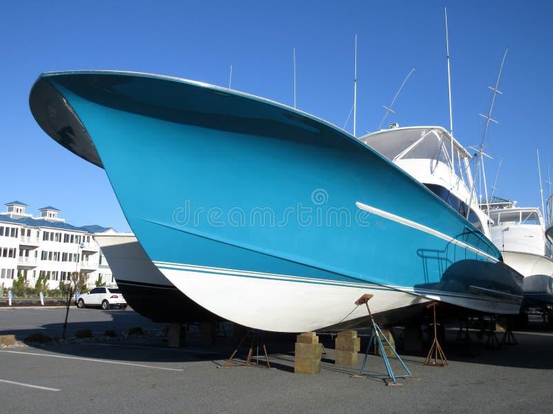 Blå sportfiskebåt i torr skeppsdocka arkivfoto