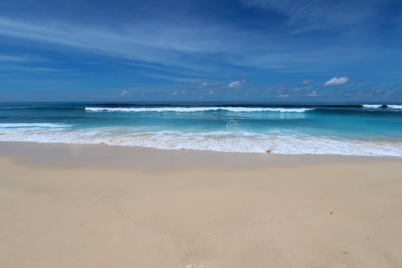 blå strand med vita sand och vågor i Bukit område, Bali royaltyfri bild