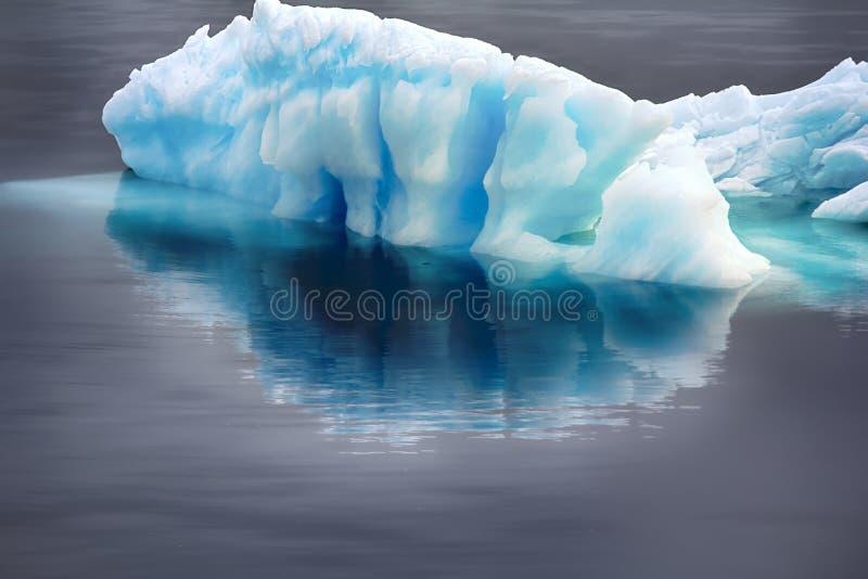 Blå surpuppa (stycke av isberget) med reflexion i lugna vatten royaltyfria foton